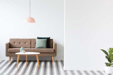 Round table in front of a brown sofa under pastel lamp in minimal living room interior