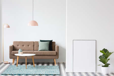 Plant next to an empty poster with mockup in vintage living room interior with brown couch Stock Photo