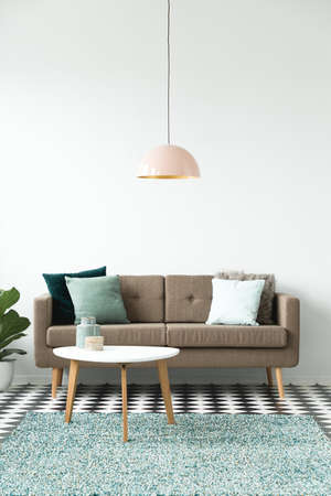Pastel lamp above white round table near brown sofa in simple living room interior 免版税图像 - 101304323