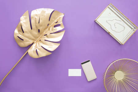Golden leaf, phone, business card and metal bowl on a purple table Stock Photo