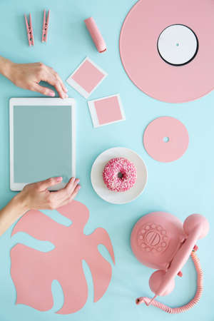 Top view of a blue desk with vintage phone, leaf, doughnut, vinyl and hands touching a tablet