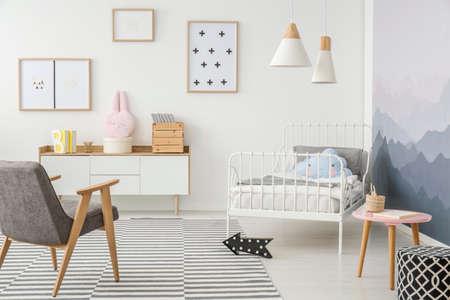 Simpatici cuscini sul letto con struttura in metallo di un bambino e semplici mobili in legno in una camera da letto dal design creativo per una ragazza Archivio Fotografico - 101304358