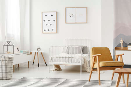 Minimalist framed posters on a white wall in a nordic style childs bedroom interior with designer decor and modern furniture
