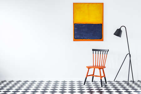 Black lamp next to duocolor chair on checkerboard wall in living room interior with painting and copy space
