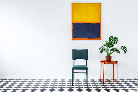 Turquoise chair next to an orange table with plant against white wall with painting in living room interior