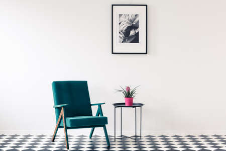 Pink flower on table next to a turquoise armchair on checkerboard floor in living room interior with poster