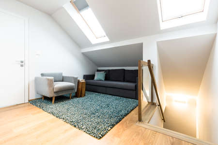 Comfortable, gray armchair and black sofa in a relax corner of a white attic house interior with roof windows Stockfoto
