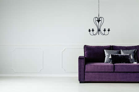 Black chandelier above violet settee in glamour living room interior with copy space on white wall