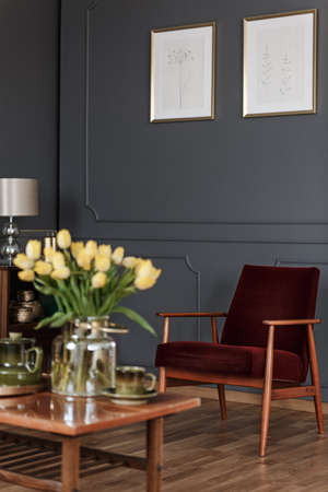 Blurred yellow flowers on wooden table in dark living room interior with posters above armchair Banco de Imagens