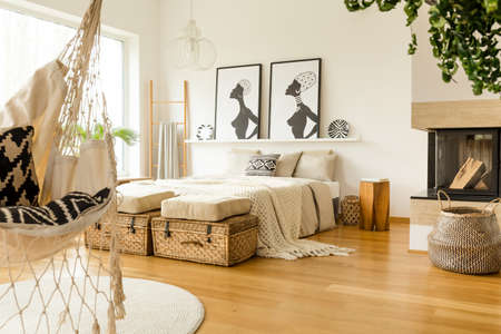 Fireplace near bed with knit blanket in boho bedroom interior with posters and rattan bag