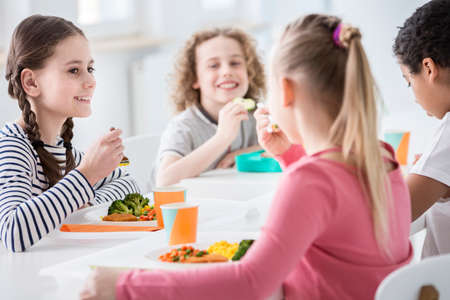 Smiling girl eating vegetables during lunch break with friends at school Archivio Fotografico