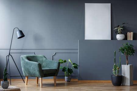 Lámpara negra junto al sillón verde en el interior de la sala de estar con plantas y maqueta de póster