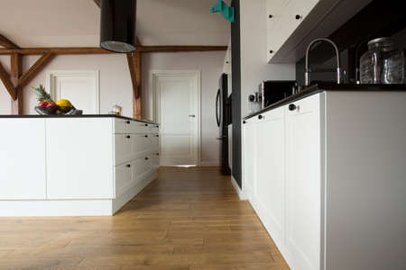 Low angle view of a modern kitchen interior with wooden floor, white cupboards and black countertop