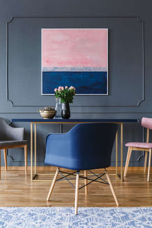 Navy blue armchair near table with flowers in grey apartment interior with pink painting