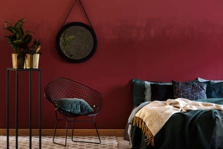 Plants and chair in dark red bedroom interior with bed against the wall with round black mirror