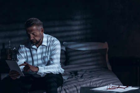 Exhausted middle-aged male sitting on a bed in a hotel room at night and looking into a notepad during his corporate business trip