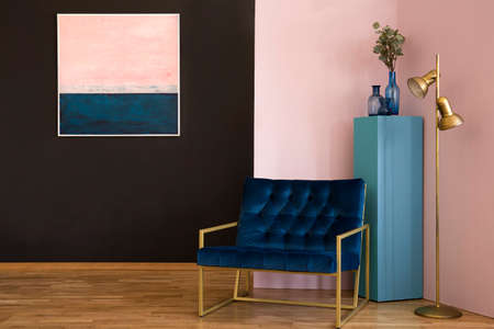 Navy blue armchair next to a gold lamp in black and pink living room interior with painting Reklamní fotografie