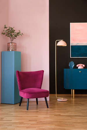 Red velvet armchair in pastel living room interior with pink lamp next to a navy blue cabinet