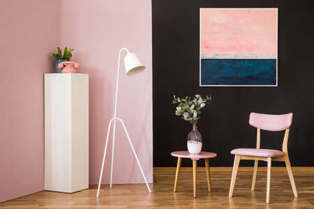 Pink chair next to a round table with plant in retro living room interior with white lamp and painting