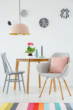 Front view of a dining table, chair, retro armchair with a pillow, colorful carpet, lamp and plates on the white wall