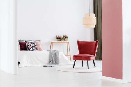 White and pink bedroom interior with elegant armchair next to a bed with white sheets 스톡 콘텐츠