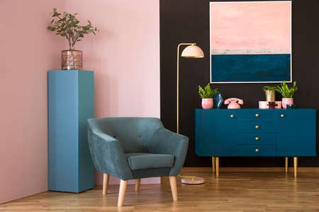 Blue suede armchair against pink wall in living room interior with cabinet under painting 스톡 콘텐츠