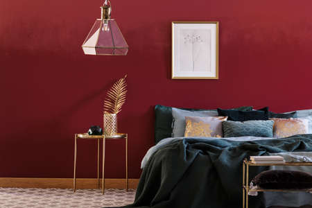 Emerald green bed against red wall with poster in bedroom interior with lamp above gold table