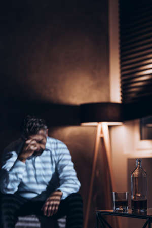 Silhouette of a stressed middle-aged man with problems sitting alone with his head down next to a bottle and a glass of alcohol in a dark room with window blinds and a dimmed light of a standing lamp