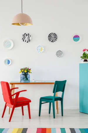 Red and green chair, plates as wall decoration, lamp, table with flowers and colorful rug in a living room interior Stock Photo