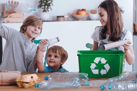 Glimlachende kinderen die plezier hebben terwijl ze plastic flessen en papier in een groene bak scheiden