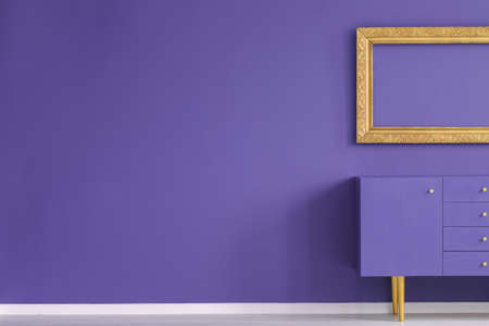 Real photo of a creative living room interior with golden frame above violet cupboard standing against an empty wall with copy space. Place for your product