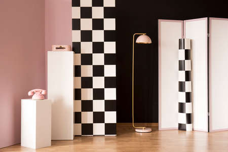 Pink phone on white pedestal in studio interior with checkerboard wall next to a lamp and screen 스톡 콘텐츠
