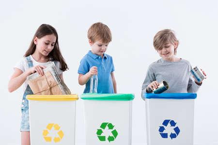 Niños que separan papel, vidrio y metal en contenedores amarillos, verdes y azules
