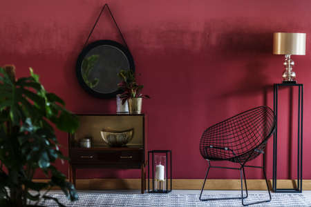 Gold lamp and black chair next to cupboard against red wall with round mirror in living room interior