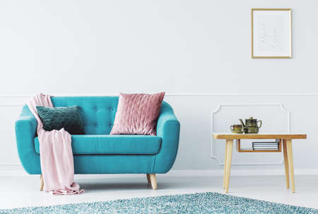 Blue sofa with pastel pink blanket and two pillows standing in bright living room interior with wall molding Stock Photo