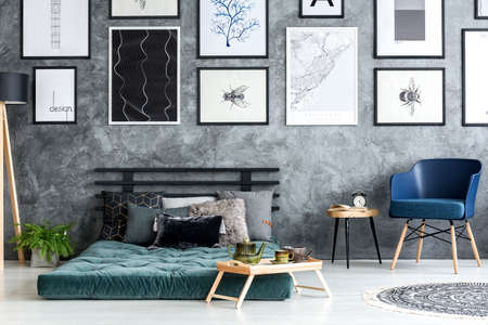 Navy blue armchair next to a wooden table in bedroom interior with posters above green futon