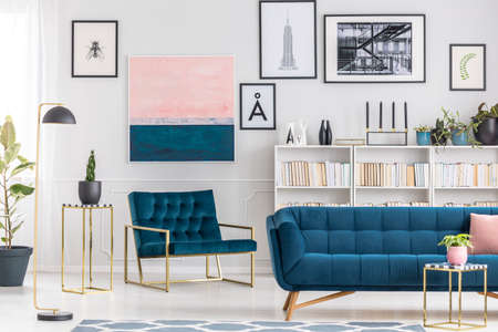 Navy blue sofa against bookshelf and white wall with pink painting in elegant living room interior