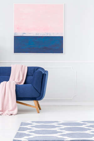 Pink blanket on navy blue sofa against white wall with painting in pastel living room interior