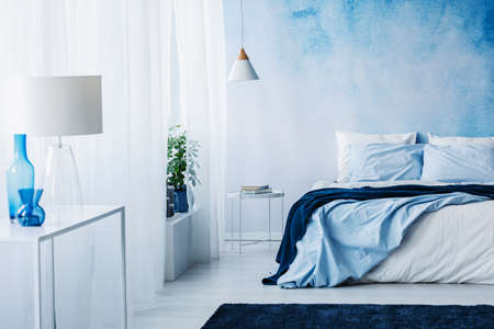 Relaxing bedroom interior with white and blue decorations, double bed and wallpaper