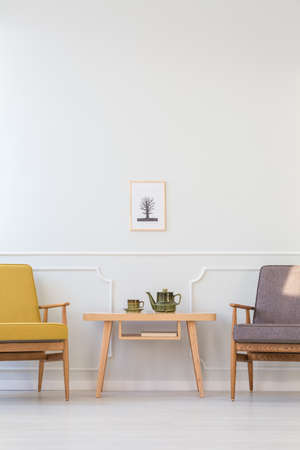 Wooden table between grey and yellow armchair against white wall with poster in living room interior
