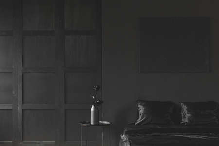 Rose on the table next to bed in monotone dark black bedroom interior with wooden molding on the wall