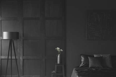 White flowers on the table between lamp and bed in black bedroom interior with molding on the wall