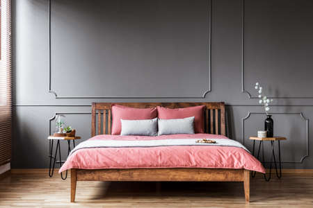 Plants on the table next to a rustic bed with pink bedsheets in bedroom interior with grey wall