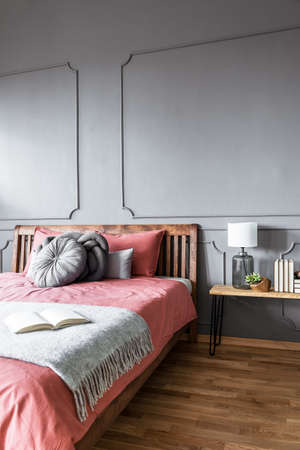 Book on blanket on wooden pink bed against grey wall with molding in cozy bedroom interior Banque d'images