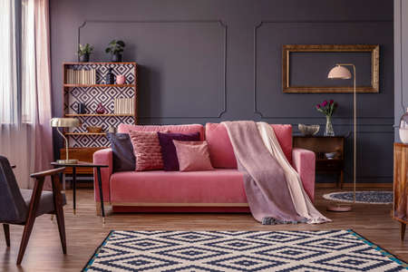 Pastel pink blanket on a matching sofa in living room interior with elegant, golden frame on a dark grey wall