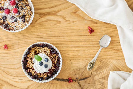 Top view of a wooden breakfast table with two bowls of oatmeal with fruit, elegant silver spoon and white cloth Stock Photo