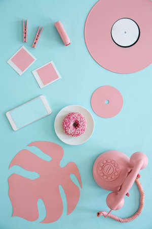 Top view of pastel table with vinyl, phone, doughnut, paper leaf and cd Archivio Fotografico - 101898869