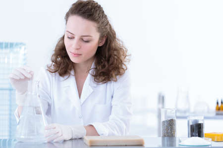 Biotechnologist dissolving the sample in a solution during laboratory analysis