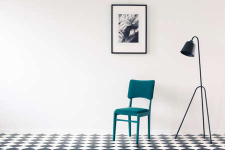 Black lamp next to turquoise chair against white wall with poster and copy space in minimal interior 版權商用圖片