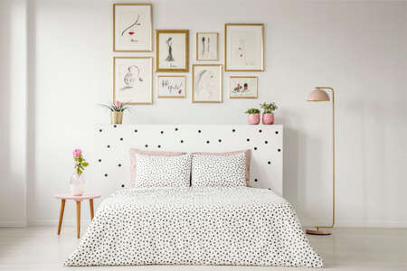 Patterned bedding on bed with bedhead in womans bedroom interior with pink flower on table